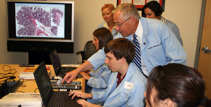 Dr. Ronald S. Weinstein works with a group of students